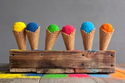 Bright colours in shapes of ice cream scoops in cones for Indian holi festival. Colorful gulal (powder colors) for Happy Holi.