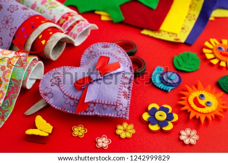 Bright crafts made of felt. Felt and crafts made of felt on a red background. Heart, sun, snail, butterfly, flowers are made of felt. Handicrafts in colorful and multi-colored colors.