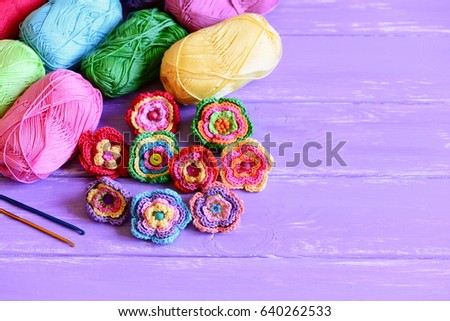 Bright crochet flowers set. Homemade crochet flowers, varicolored cotton yarn, crochet hooks on wooden background with copy space for text. Easy handmade crochet crafts concept