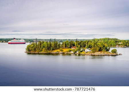 Bright cruise ship Viking line is going among archipelago in Sweden. Green scandynavian nature and red cozy houses in the foreground. Blue water and cloudy sky.