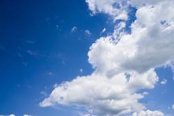 Bright cumulus clouds against a blue sky.