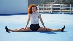 Bright curly red-haired sports model with red beautiful lips smiles and looks at the photographer. Funny flexible dancer sitting in split, blue floor and in the background