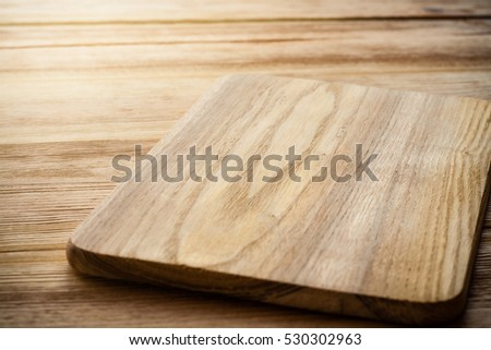 Bright cutting board on a background of the wooden table #530302963
