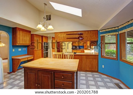 Bright dining area with blue walls, white vaulted ceiling with skylight. View of kitchen island