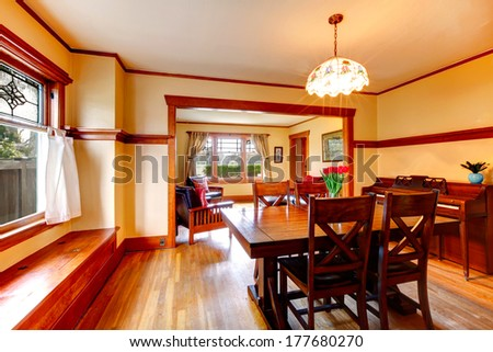 Photo of Bright dining room with rustic dining table with fresh flowers, chairs and piano. Open wall design with living room