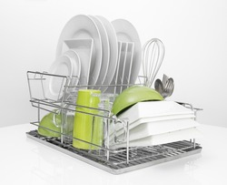 Bright dishes drying on a metal dish rack. White background.