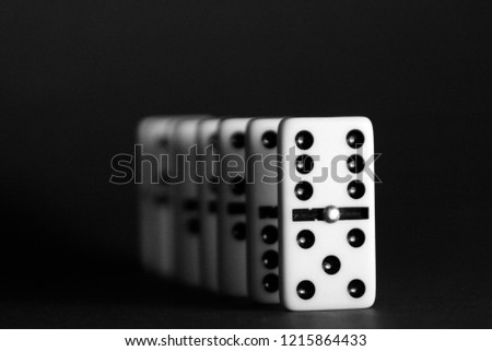Bright dominoes against a black background with shallow depth of field as a concept for business concepts and subsequent reactions of individual decisions and individual actions
