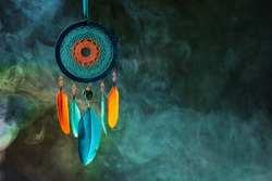 Bright dreamcatcher on dark abstract background