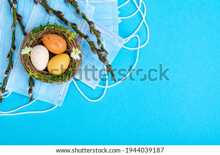 Bright Easter eggs, medical masks, willow branches on colored background. Quarantine Easter. Stop COVID-19 VIRUS. Studio Photo
