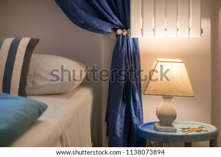 Bright eco light in the corner of a modern bedroom. New led technology meets traditional interior design. Lamp is creating cozy atmosphere in room. Wooden, glass table, blue curtains