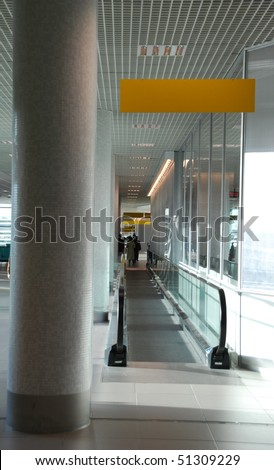 bright entrance on a moving escalator and yellow sign in a international airport