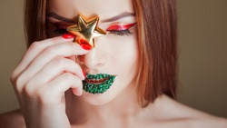Bright eye makeup and green lips in rhinestones. Unusual look with bright red arrow on her eyes and with a gold star . Close up
