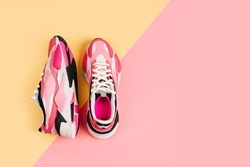 Bright female sneakers on pink background. Fashion blog or magazine concept. Women's shoes, trendy sneakers, fashion, style, lifestyle. Flat lay top view copy space minimal background.