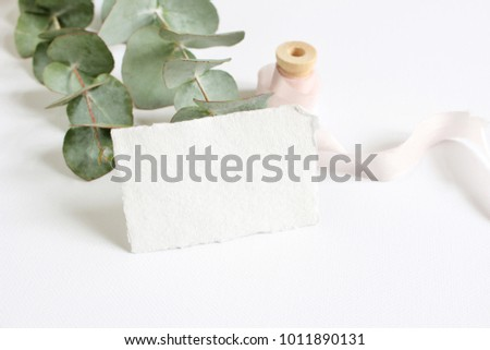 Bright feminine spring stationery mockup scene with a handmade paper greeting card, spool of silk ribbon and eucalyptus leaves on a white table background. Wedding styled stock photography.