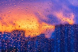 Bright fiery sunset through raindrops on window with bokeh lights. Abstract background. Water drop on the glass against the blurred silhouettes high-rise city. Selective focus noise