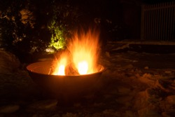 Bright fire in the outdoor fire pit on a snowy winter night