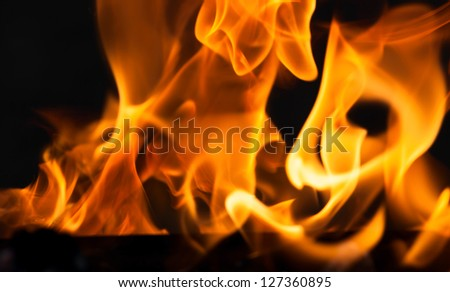 Bright flame isolated on black background - stock photo