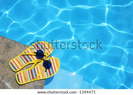Bright Flip-flops and sunglasses by swimming pool #1344471