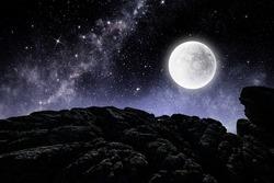 Bright full moon over dark mountain