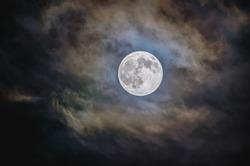 Bright full moon with cloudy background at the nighttime