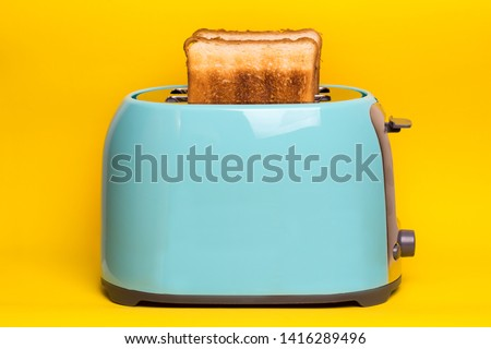 bright, fun breakfast. cyan color toaster on a yellow background