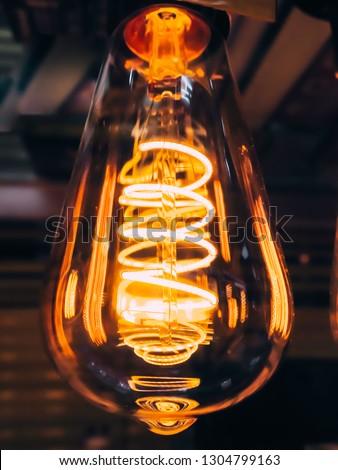 Bright glowing clear glass lamp pear shaped close up. Illumination edison retro lamp dark background. Antique vintage filament light bulb. #1304799163