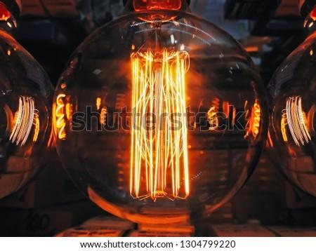 Bright glowing clear glass lamp spherical shape close up. Illumination edison retro lamp dark background. Antique vintage filament light bulb. #1304799220