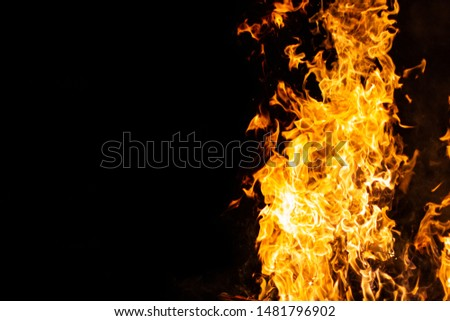 bright glowing flames on a black background on the right side of the picture