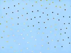 Bright gold stars on a blue background with sequins. The concept of a holiday, joy. Festive background for your projects