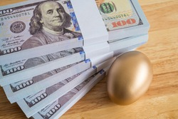 Bright golden egg and US dollar bill cash banknotes background. Rich, wealth, successful from stock dividend in stock market investment. Business, financial, investment and retirement planning concept
