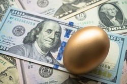 Bright golden egg on US dollar bill banknotes background. Rich, wealth, successful from stock dividend yield in stock market investment. Business, financial, investment and retirement planning concept