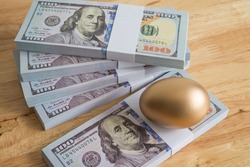 Bright golden egg on US dollar bill cash banknotes background. Rich, wealth, successful from stock dividend in stock market investment. Business, financial, investment and retirement planning concept.