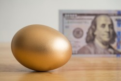 Bright golden egg with US dollar bill cash banknote background. Rich, wealth, successful from stock dividend in stock market investment. Business, financial, investment and retirement planning concept