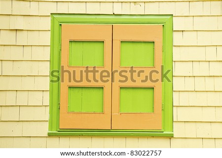 Bright green and orange shutters on a yellow siding house