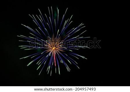 Bright green and purple fireworks against dark night sky.