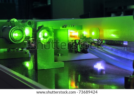 bright green laser light going inside complicate scientific system with cooling hoses inside