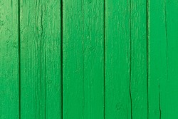 Bright green wooden background with peeling paint and vertical boards