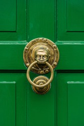 Bright green wooden door with a solid brass stylised vintage face door knocker ring.