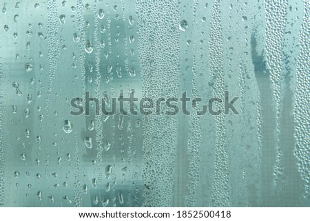 Photo of  Bright grey color glassy texture, with water drops on it. Water drop glassy background