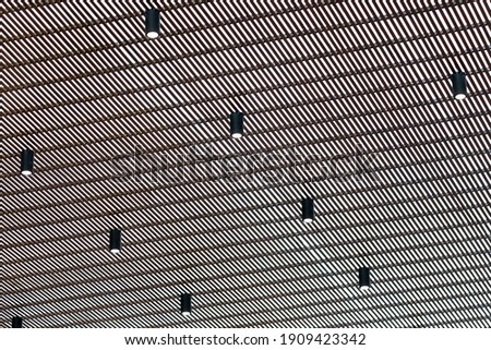 Bright halogen spotlight on the ceiling grille. Abstract background. Stock photo ©