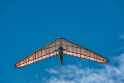 Bright hang glider wing silhouette from below. Extreme sport.