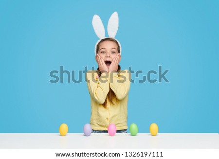 Bright happy girl in white bunny ears standing in great amazement on blue background with Easter eggs on table