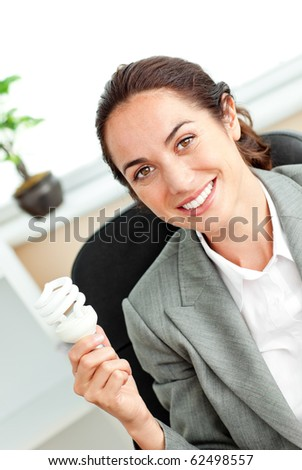 Bright hispanic businesswoman holding a light bulb sitting at her desk in her office