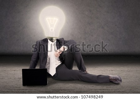 Bright idea concept: Businessman with head made of lightbulb sitting on the floor with laptop