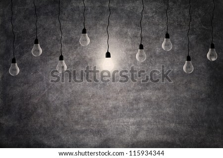 Bright idea concept: on and off light bulbs in front of empty blackboard with copy space