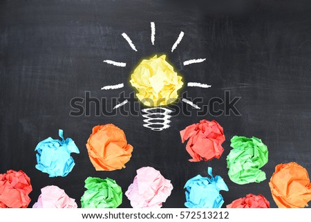 Bright idea concept with light bulb shaped crumpled paper on blackboard  #572513212