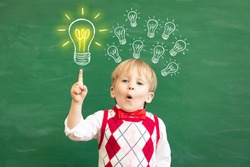 Bright idea! Surprised child student pointing finger up! Happy kid against green chalkboard. Online education and e-learning concept. Back to school