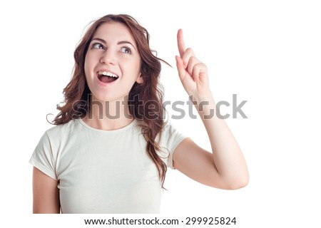 Bright idea. Upbeat pretty young girl holding finger raised and looking up while feeling illuminated.
