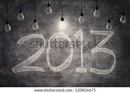 Bright ideas of 2013 represent by light bulbs on blackboard background