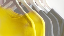 Bright illuminating yellow and gray colours clothes on hangers. Trendy colors of the year 2021 - Gray and Yellow. Fashionable clothes colors.